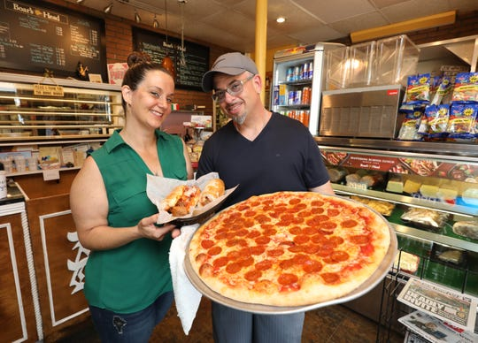Owners Kelly and Lance Bieber show off a Shweaty Cheesy Balls hero and a pepperoni pizza at B-Balls Meatballs on Prairie Avenue in Suffern, Aug. 15, 2018.