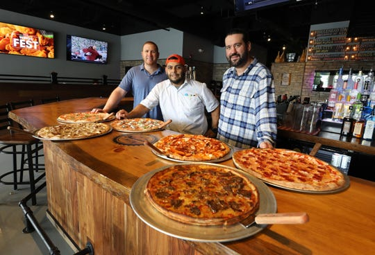 Life before the coronavirus: Norcina owners Nick Nuccio, Chef Erick Carrasco and Milan Dobrilovic, pictured at their New City restaurant with some of their pizzas.