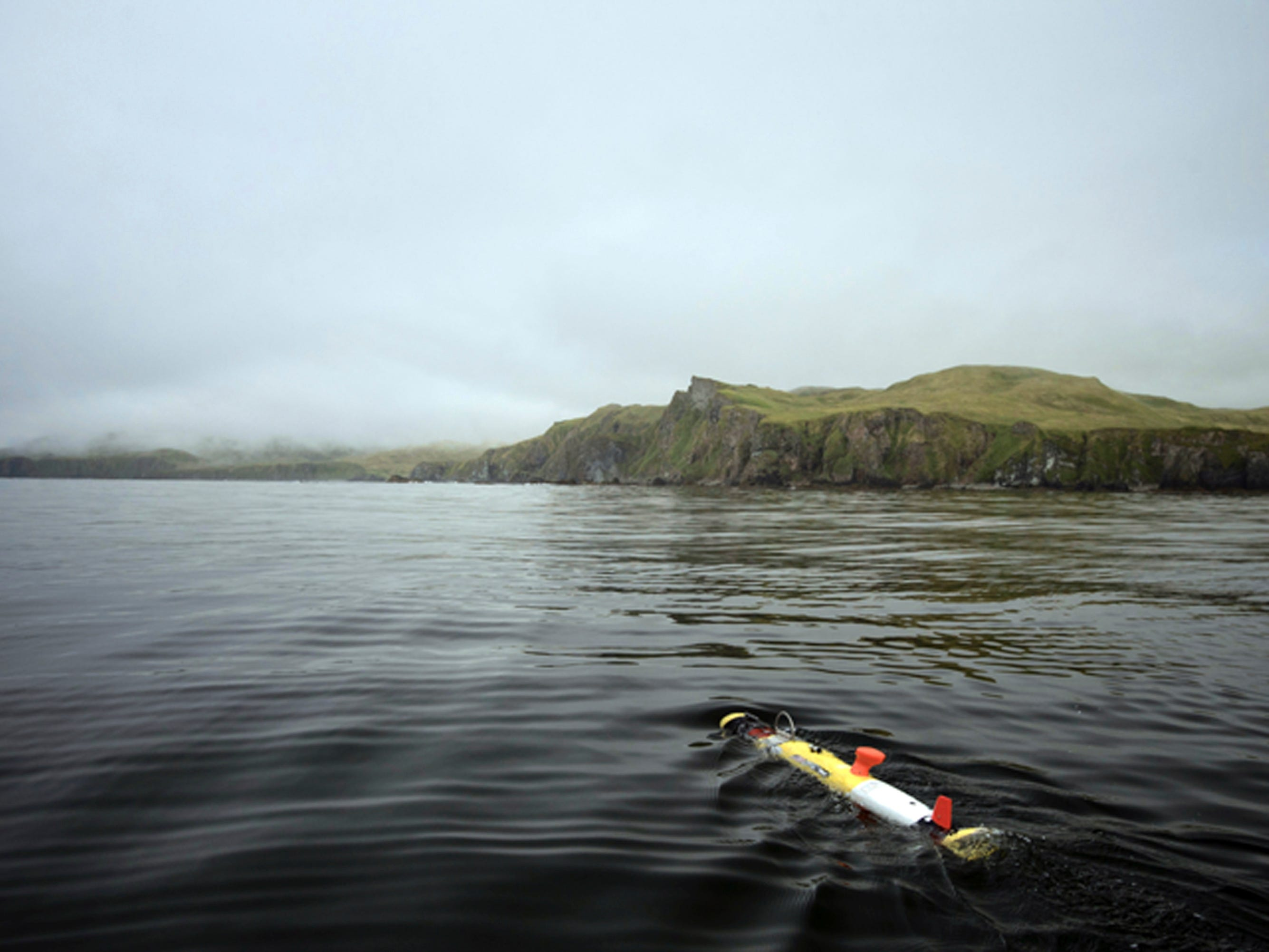 In this July 18, 2018 photo provided by Project Recover, a Remote Environmental Monitoring Units (REMUS) glides away from a research boat before diving beneath the surface where it spent the next six hours systematically scanning the seafloor, searching for the stern of the destroyer USS Abner Read in the waters off Kiska Island, Alaska. The Abner Read hit a mine left by the Japanese after they abandoned Kiska Island in Alaska's Aleutian Islands in 1943, ripping the stern off. But the ship never sank and was refitted and returned to duty. Now, 75 years after the ship's stern broke off, it has been located off Kiska by a team of scientists funded by the U.S. government. (Project Recover via AP)