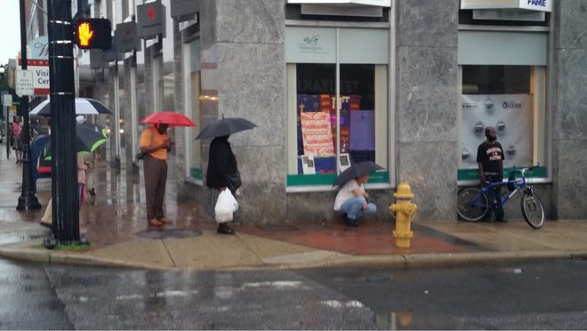 People wait in the rain for their bus on the corner of Orange Street in downtown Wilmington. Some routes have been redirected to Orange Street since bus routes involving Rodney Square were changed.