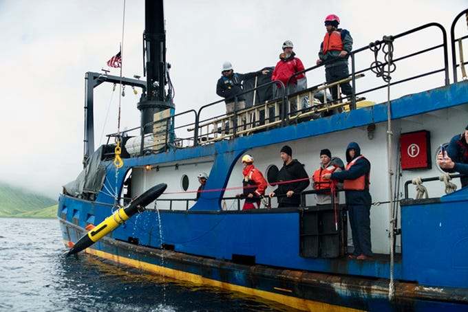 In this July 14, 2018 photo provided by Project Recover, scientists deploy one of four Remote Environmental Monitoring Units (REMUS) as they search for the stern of the destroyer USS Abner Read in the waters off Kiska Island, Alaska. The Abner Read hit a mine left by the Japanese after they abandoned Kiska Island in Alaska's Aleutian Islands in 1943, ripping the stern off. But the ship never sank and was refitted and returned to duty. Now, 75 years after the ship's stern broke off, it has been located off Kiska by a team of scientists funded by the U.S. government. (Project Recover via AP)