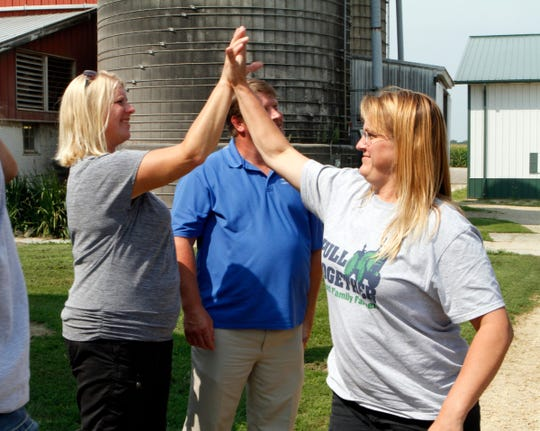 Julianne Kreager is greeted by National Farmers Union Vice President Patty Edelburg and Wisconsin Farmers Union President Darin Von Ruden as she gets of the bus from an Open Dairy Meeting in Albany, New York.