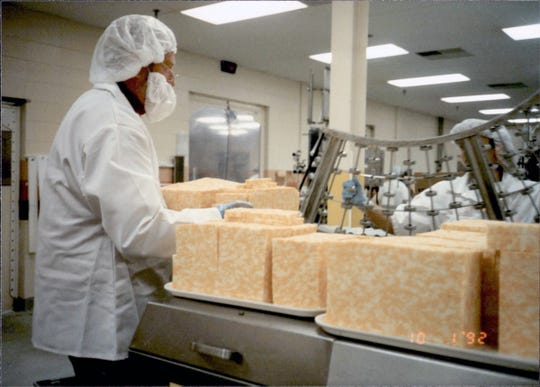 Making big pieces of cheese into consumer size cuts.