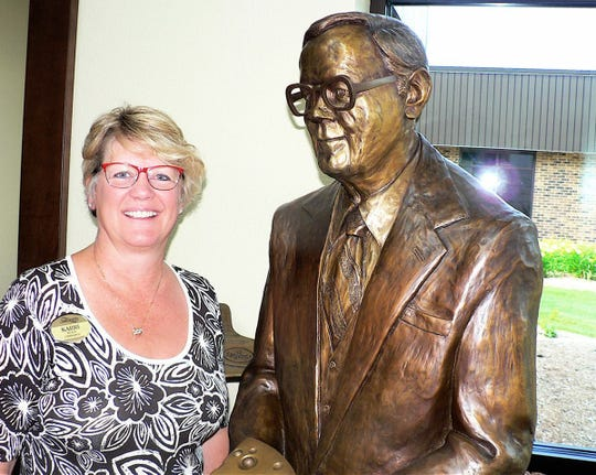 Karri Neils, recently retired VP of Human Resources at Sargento stands next to the statue of Leonard Gentine that graces the company front entrance in Plymouth.