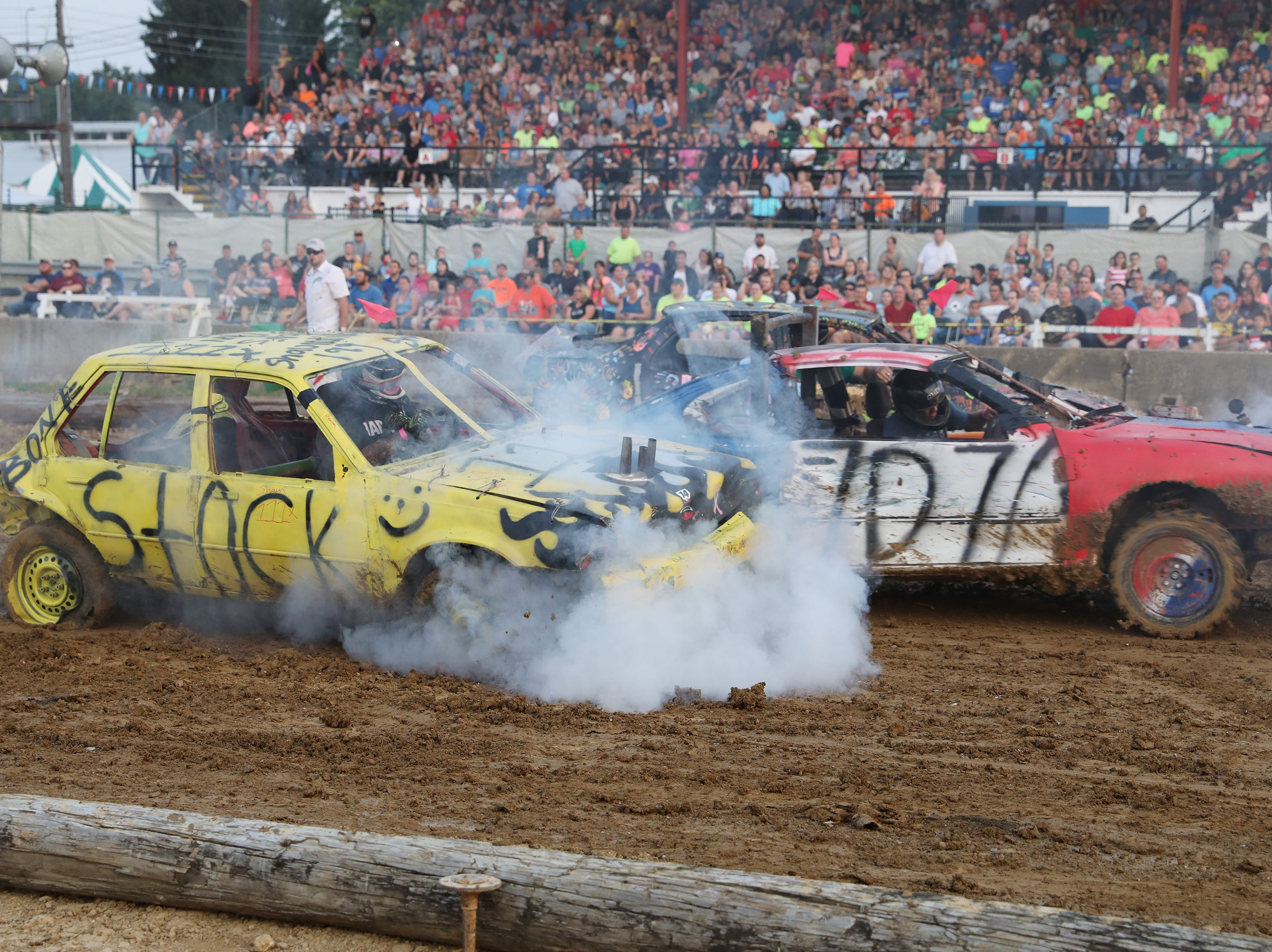 Robert Schriner's 707 car and Shawn Savage's 111x car tangle during the Sarge and Sons Demolition Derby at the Muskingum County Fair on Tuesday.