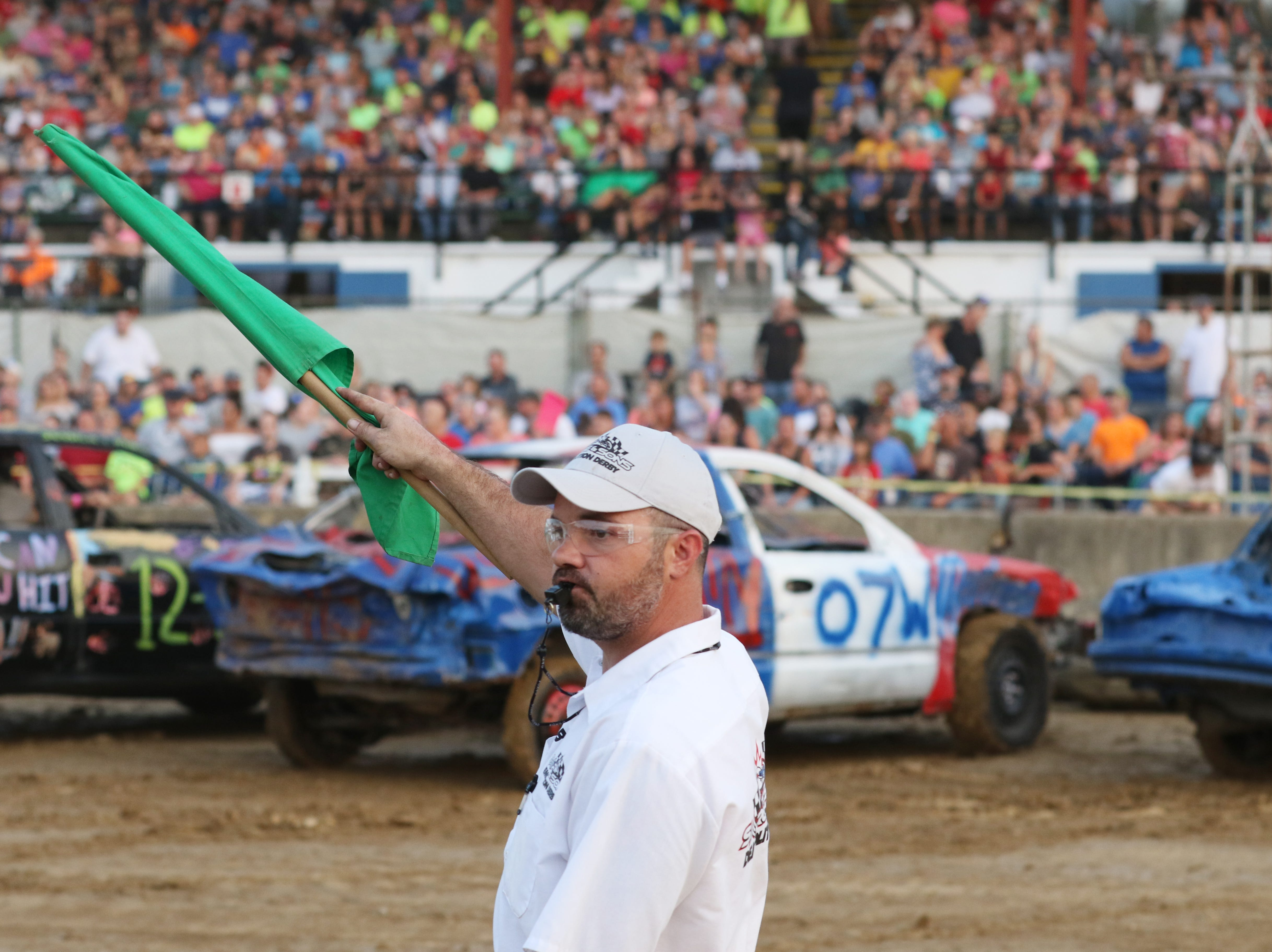 A track offical counts down the start of the Sarge and Sons Demolition Derby at the Muskingum County Fair on Tuesday.