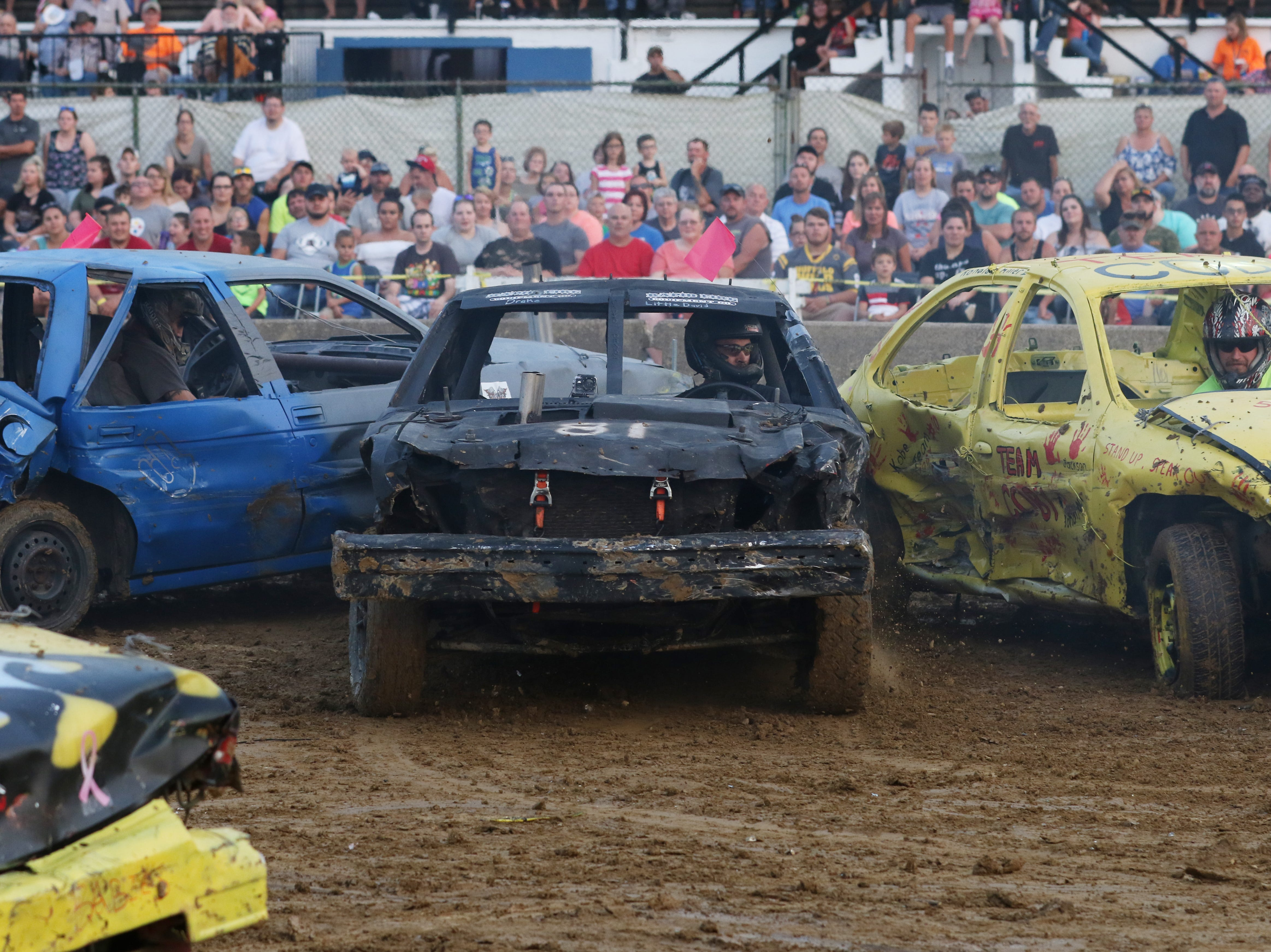 Dusty Dady finds himself between two cars during the Sarge and Sons Demolition Derby at the Muskingum County Fair on Tuesday.