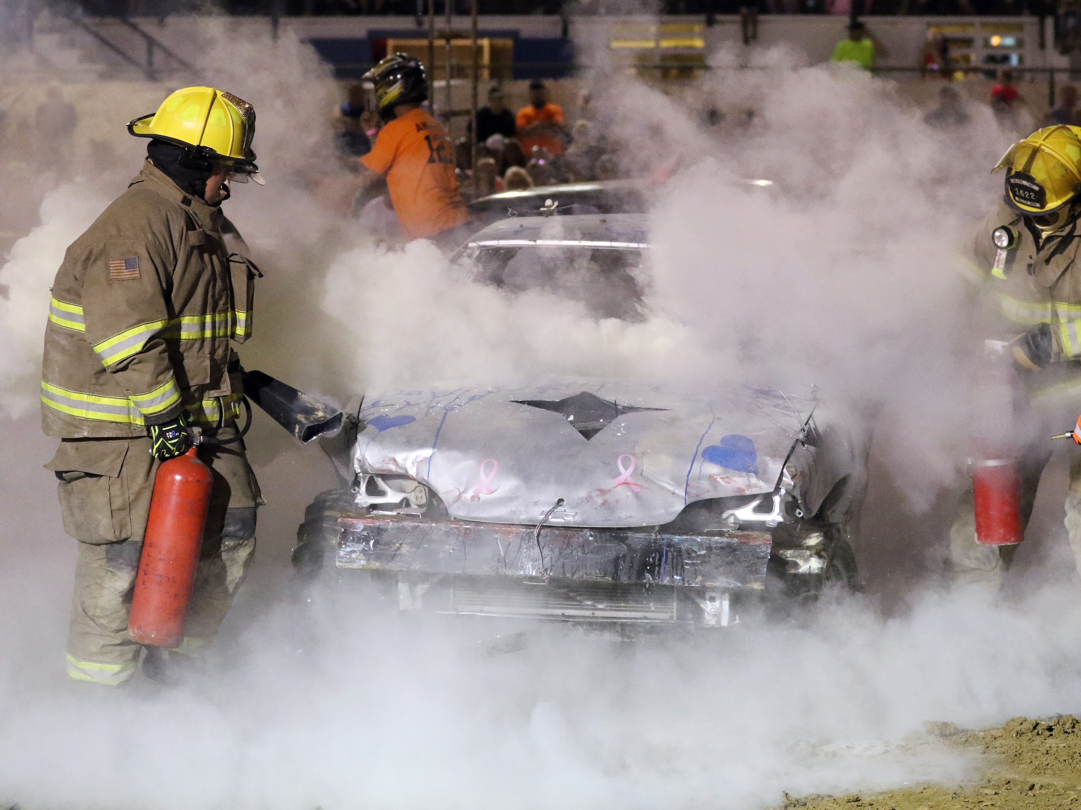 Firefighters make quick work of the flames from Brian Paul's '99 Honda Robert Anderson's 810 car and Brian Paul's 913 battle to the end of the third heat during the Sarge and Sons Demolition Derby at the Muskingum County Fair on Tuesday.