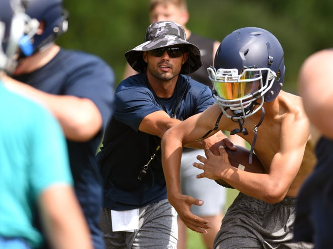 Morgan coach Chase Bowman hands the ball off to a running back during a recent practice at the high school. Bowman, a former Raider and Otterbein standout, is trying to change the program's culture.