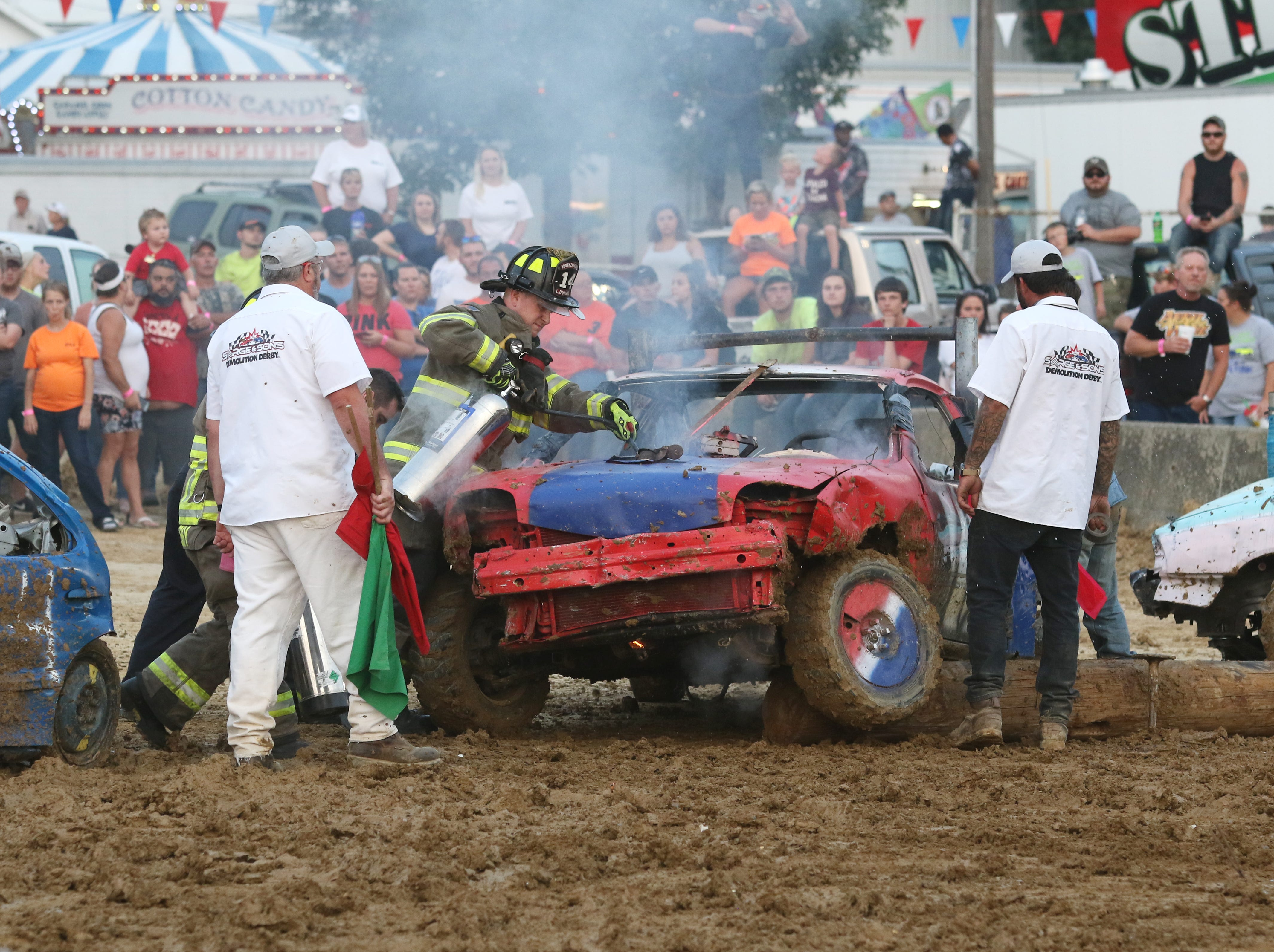 Fire and track officials tend to a car with a minor fire during the Sarge and Sons Demolition Derby at the Muskingum County Fair on Tuesday.