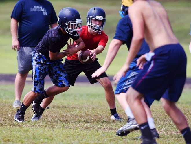 Morgan quarterback Lucas Waters reads the defensive end during an option play during a recent practice session at the high school. Waters and the Raiders are hoping to rebuild their program under first-year coach Chase Bowman.