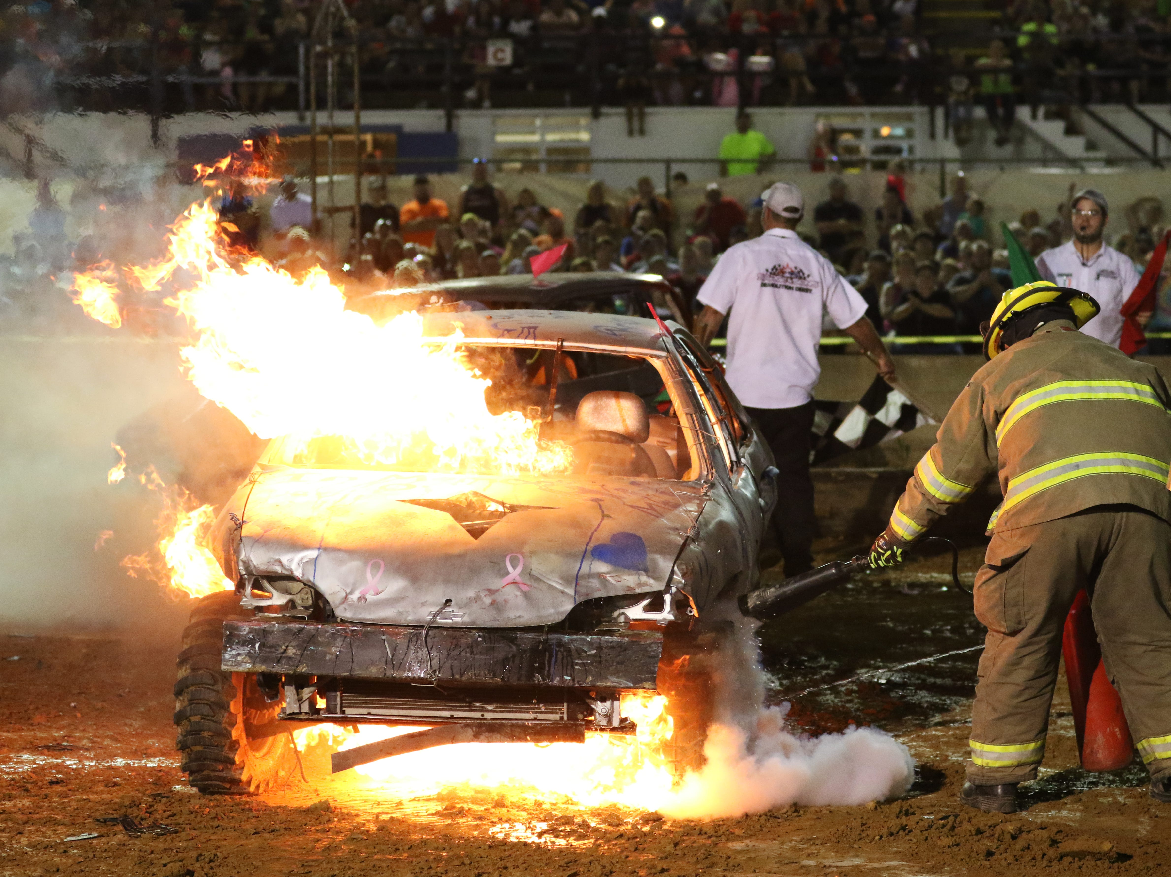 Brian Paul's '99 Honda bursts into flame Robert Anderson's 810 car and Brian Paul's 913 battle to the end of the third heat during the Sarge and Sons Demolition Derby at the Muskingum County Fair on Tuesday.