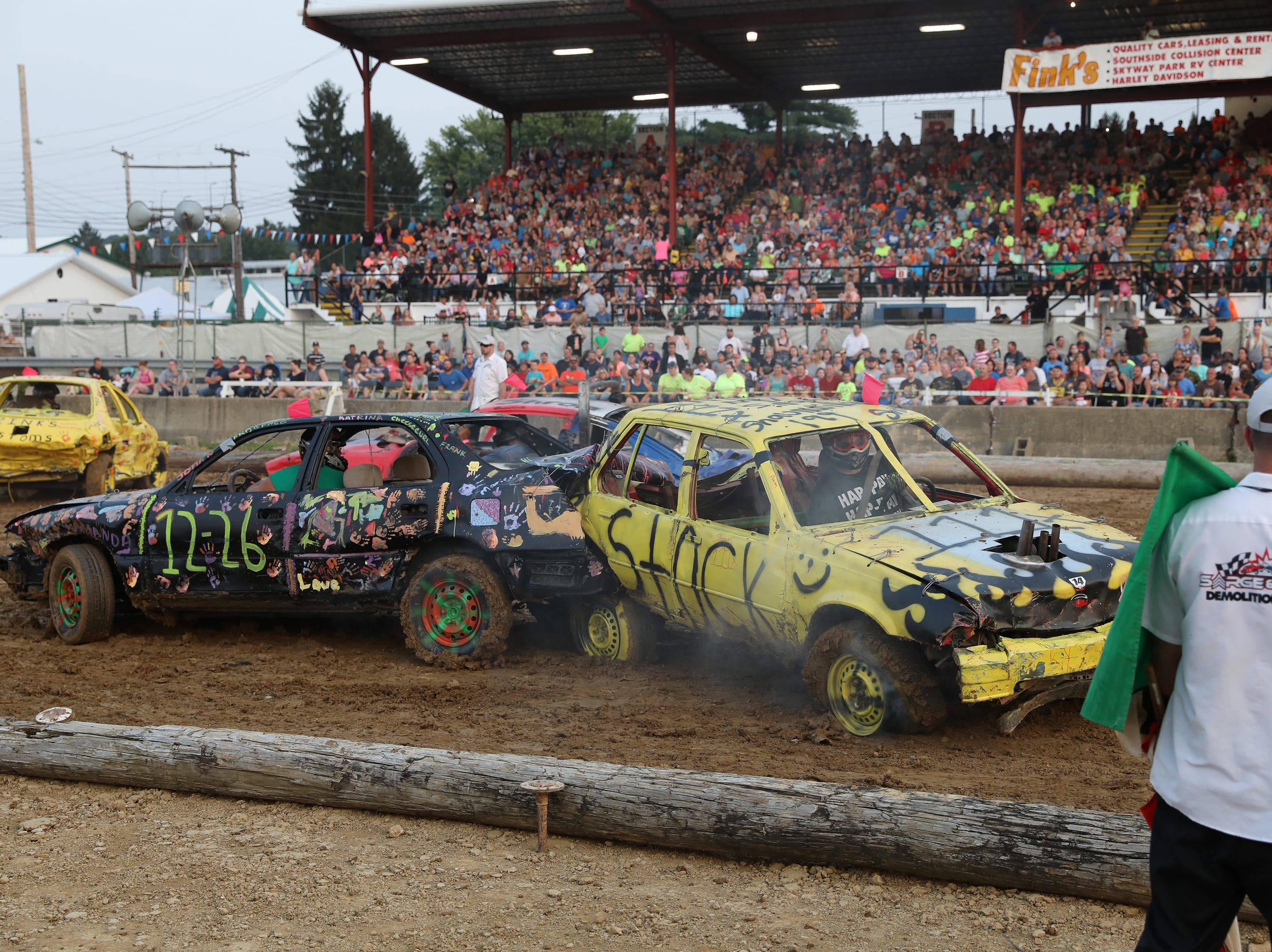 Jimmy Gibson in his 1226 and Shawn Savage in his 111x car tangle during the Sarge and Sons Demolition Derby at the Muskingum County Fair on Tuesday.