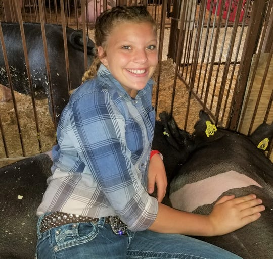 Shelby Brown sits in the pen with her show hogs, Bernie and Roscoe.