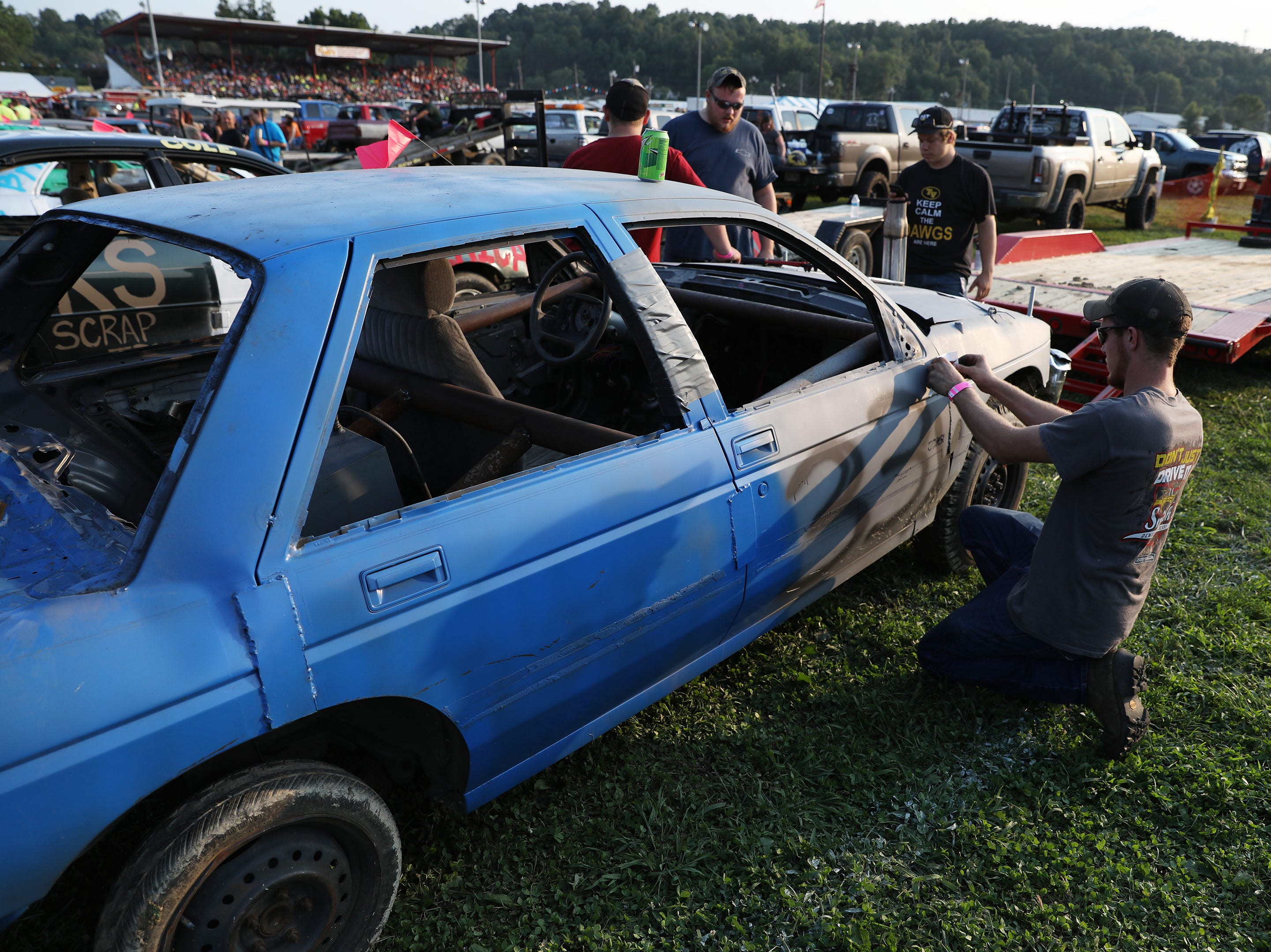 Scott Cordle puts a sticker on his before the Sarge and Sons Demolition Derby at the Muskingum County Fair on Tuesday.