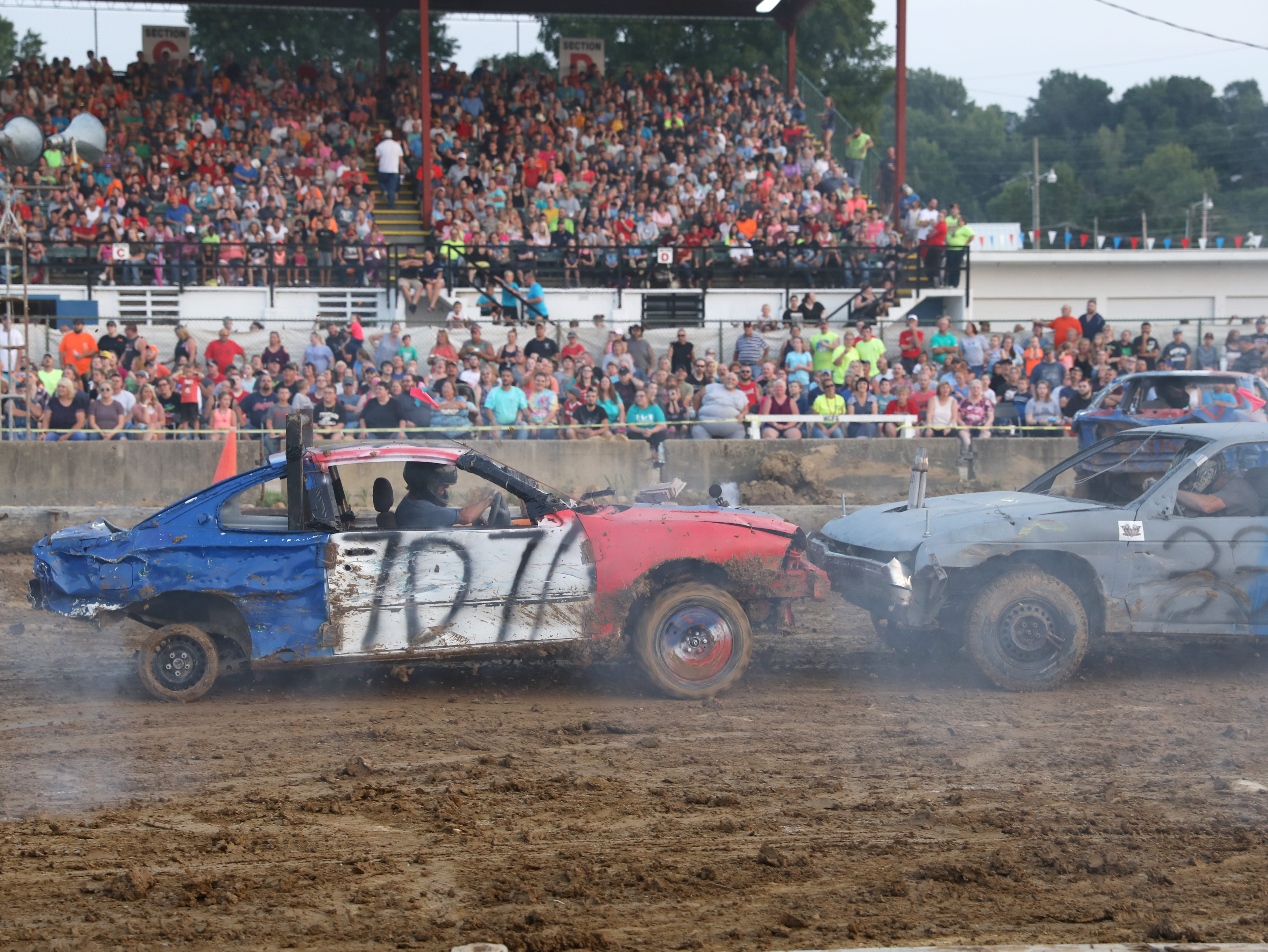 Robert Schrinder's 707 car and Scott Cordle's 33x car head on during the Sarge and Sons Demolition Derby at the Muskingum County Fair on Tuesday.