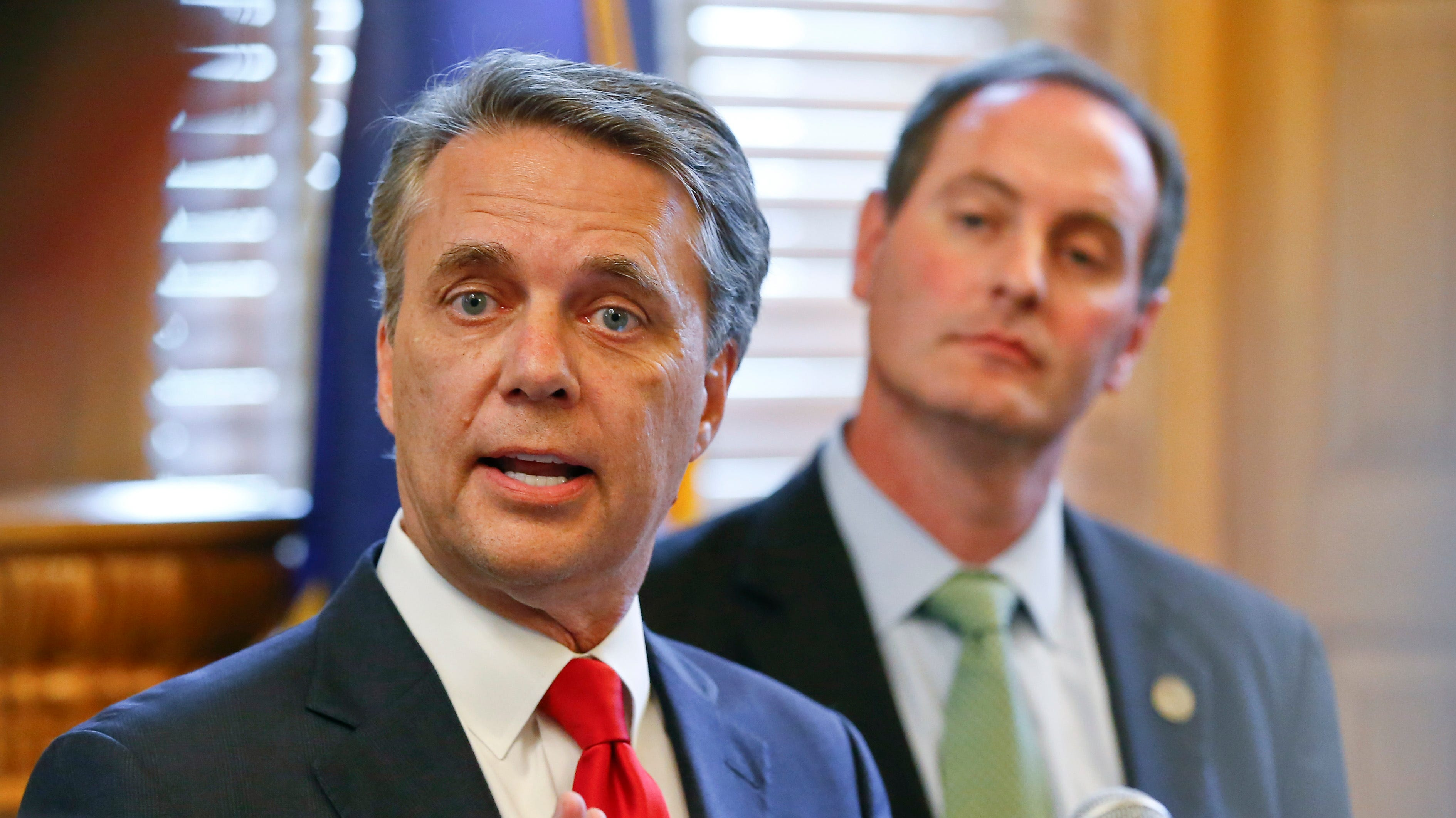 In this Aug. 8, 2018, file photo, Kansas Gov. Jeff Colyer, left, alongside Lt. Gov. Tracey Mann, addresses the media at the Kansas Statehouse in Topeka, Kan., a day after his primary race against Kansas Secretary of State Kris Kobach.