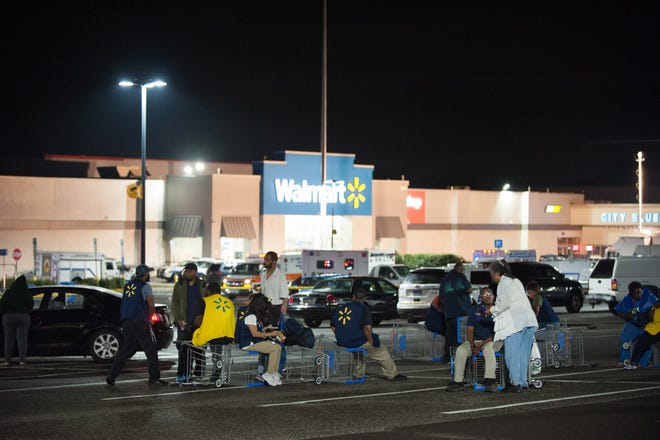 Employees and bystanders wait in the parking lot after reports of an active shooter at a Walmart in Cheltenham, Pennsylvania, 14 August 2018.