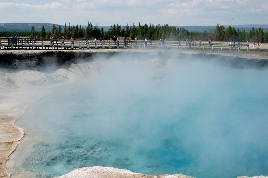 Visitors walk the boardwalk around one of Yellowstone National Park's many hot springs, which are all fueled by the heat from a supervolcano lurking far beneath the surface.