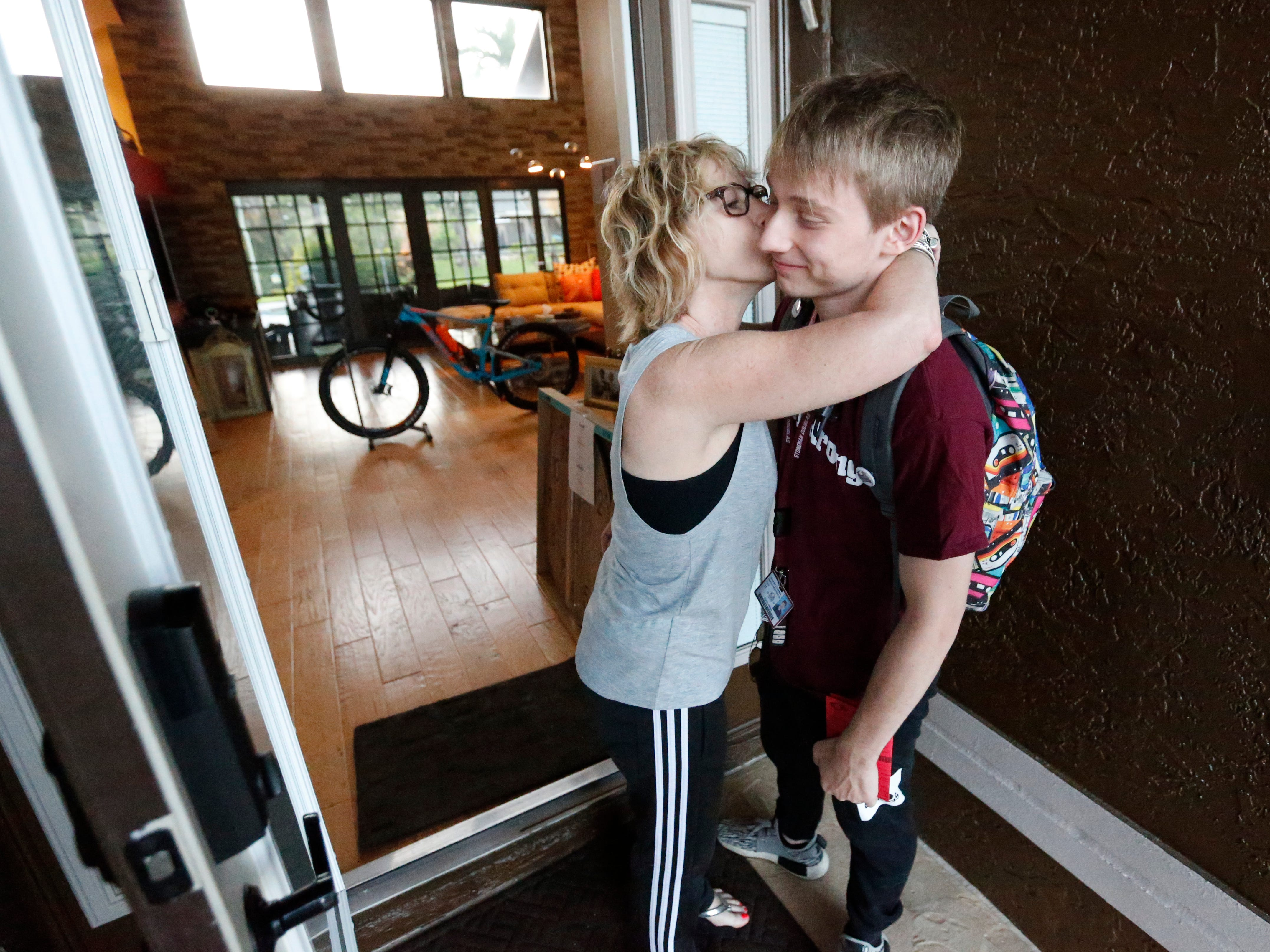 Charlie Shebes, right, 16, a junior at Marjory Stoneman Douglas High School, gets a kiss from his mother Amy as he leaves for school, Weds. , Aug. 15, 2018, in Parkland, Fla. Shebes was at the school last year when several of his classmates were shot.  Now, he's going back. Students at the school returned Wednesday, to a more secure campus as they began their first new school year since a gunman killed 17 people in the freshman building.