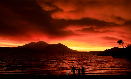 Evacuees Ken Bennett, Ember Reynolds, 8, and Lisa Reynolds watch the sunset as smoke from the Ranch Fire rises into the sky at Austin Park Beach in California's Clearlake with Mount Konocti in the background.