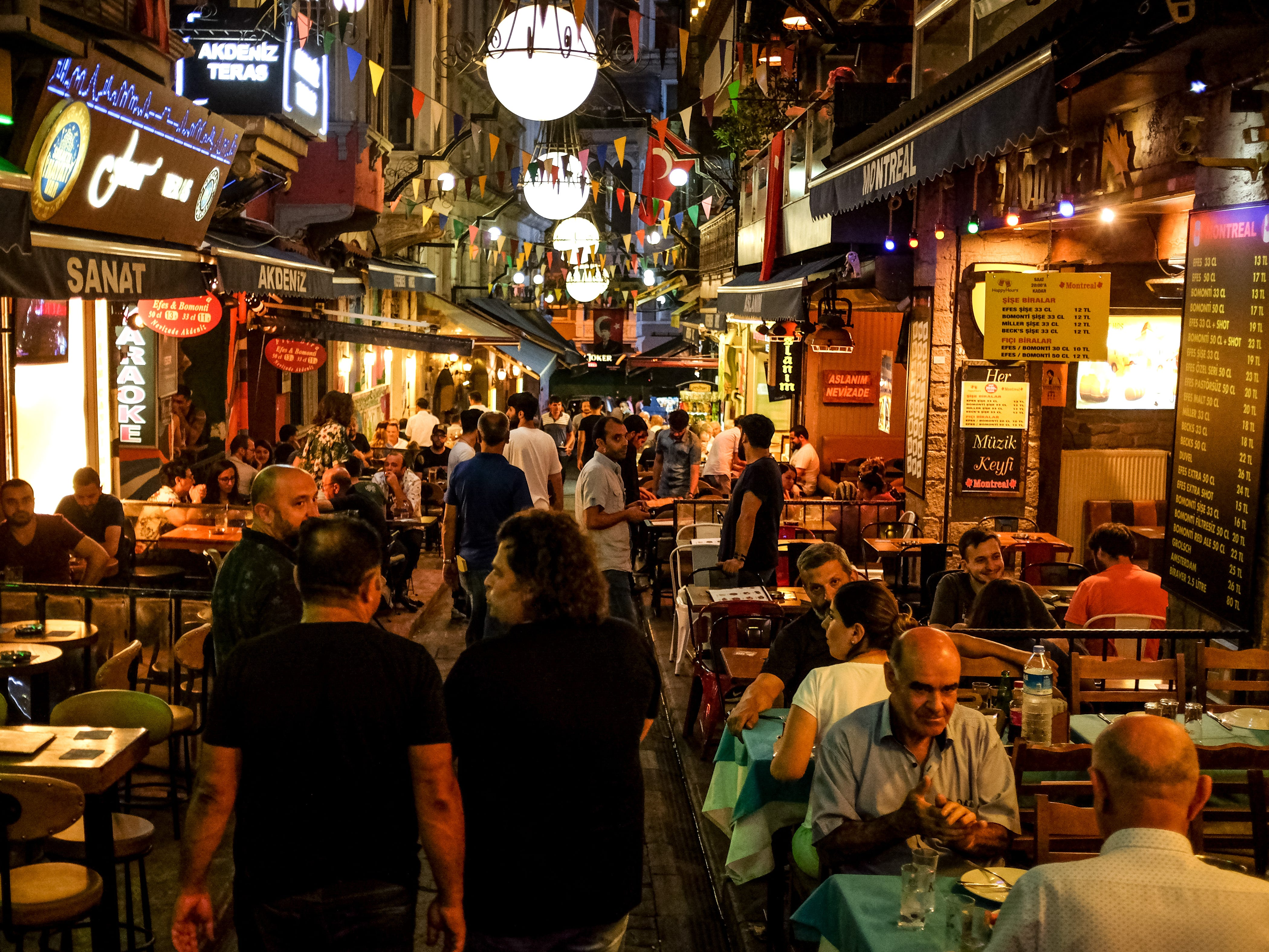 People enjoy food and drink at a popular restaurant street on Aug. 15, 2018 in Istanbul.