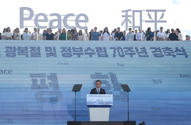 "South Korean President Moon Jae-in delivers a speech as characters and letters reading ""Peace"" are set on the top of stairs during a ceremony marking the 73rd anniversary of liberation from Japanese colonial rule in 1945, at the National Museum of Korea in Seoul on August 15, 2018."