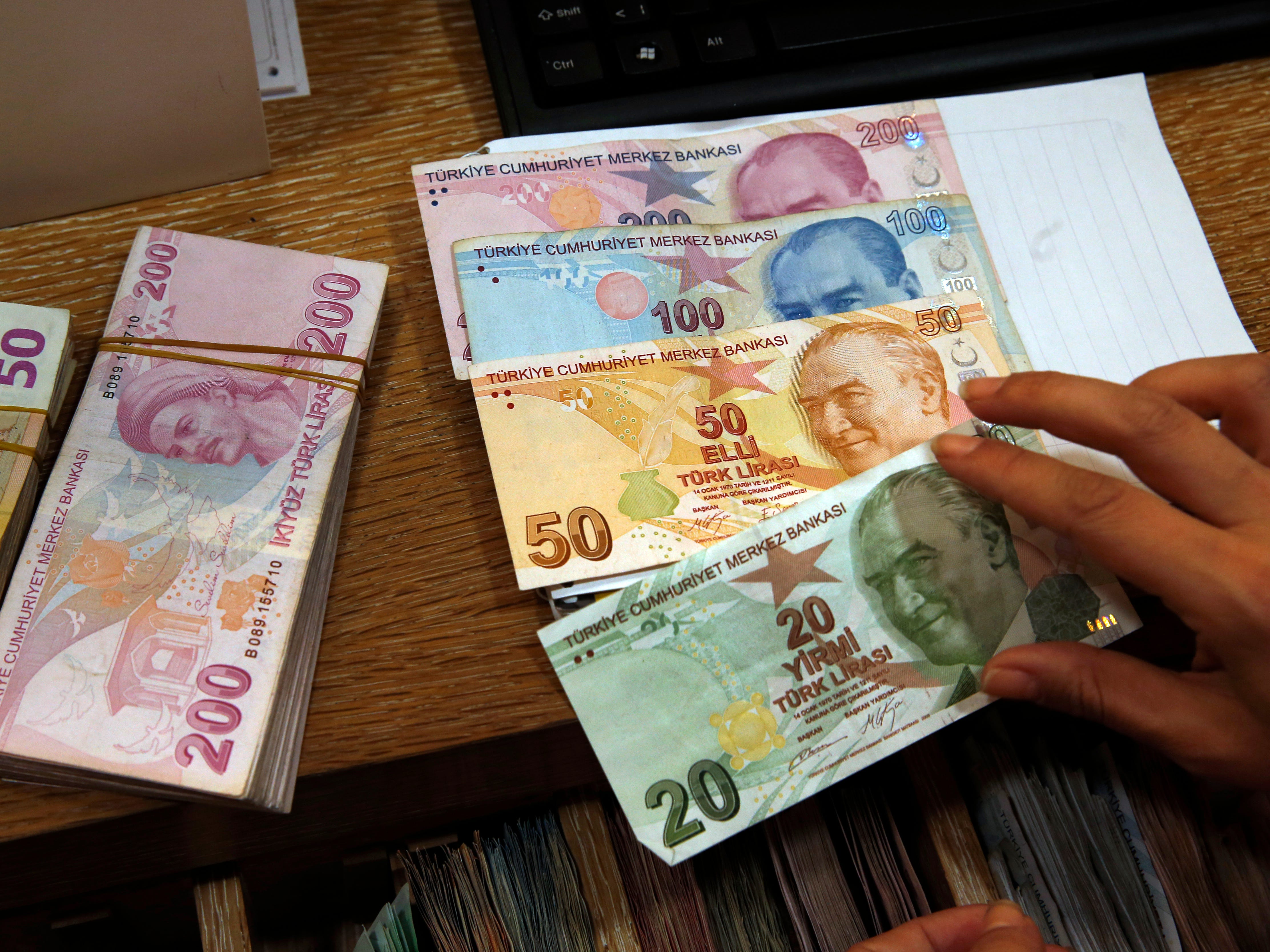 A worker at a currency exchange shop worker lays out Turkish lira banknotes depicting modern Turkey's founder Mustafa Kemal Ataturk, in Istanbul, Aug. 15, 2018.