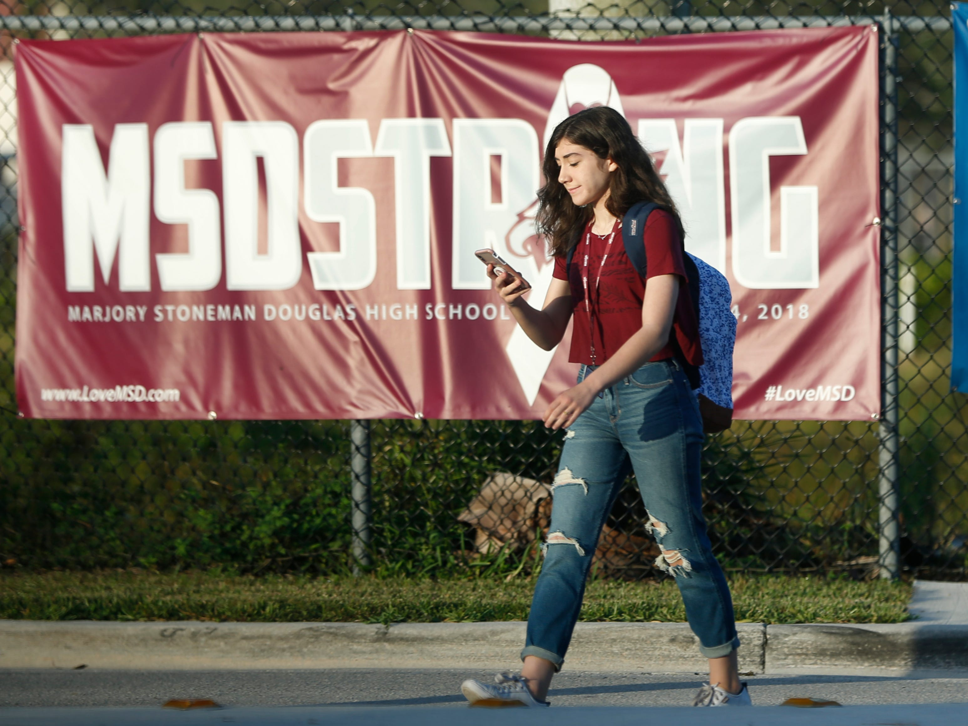 "A student walks past an ""MSDSTRONG"" banner on the way to class at Marjory Stoneman Douglas High School, Weds., Aug. 15, 2018, in Parkland, Fla."