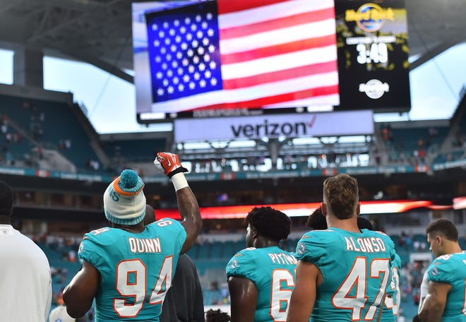 Miami Dolphins defensive end Robert Quinn raises his fist during the national anthem prior to a preseason game this month.