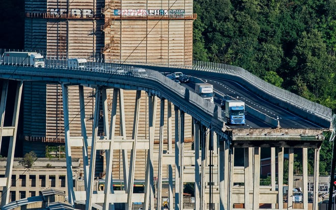 Cars and trucks are left on a section of the collapsed Morandi highway bridge in Genoa, northern Italy, Wednesday, Aug. 15, 2018.