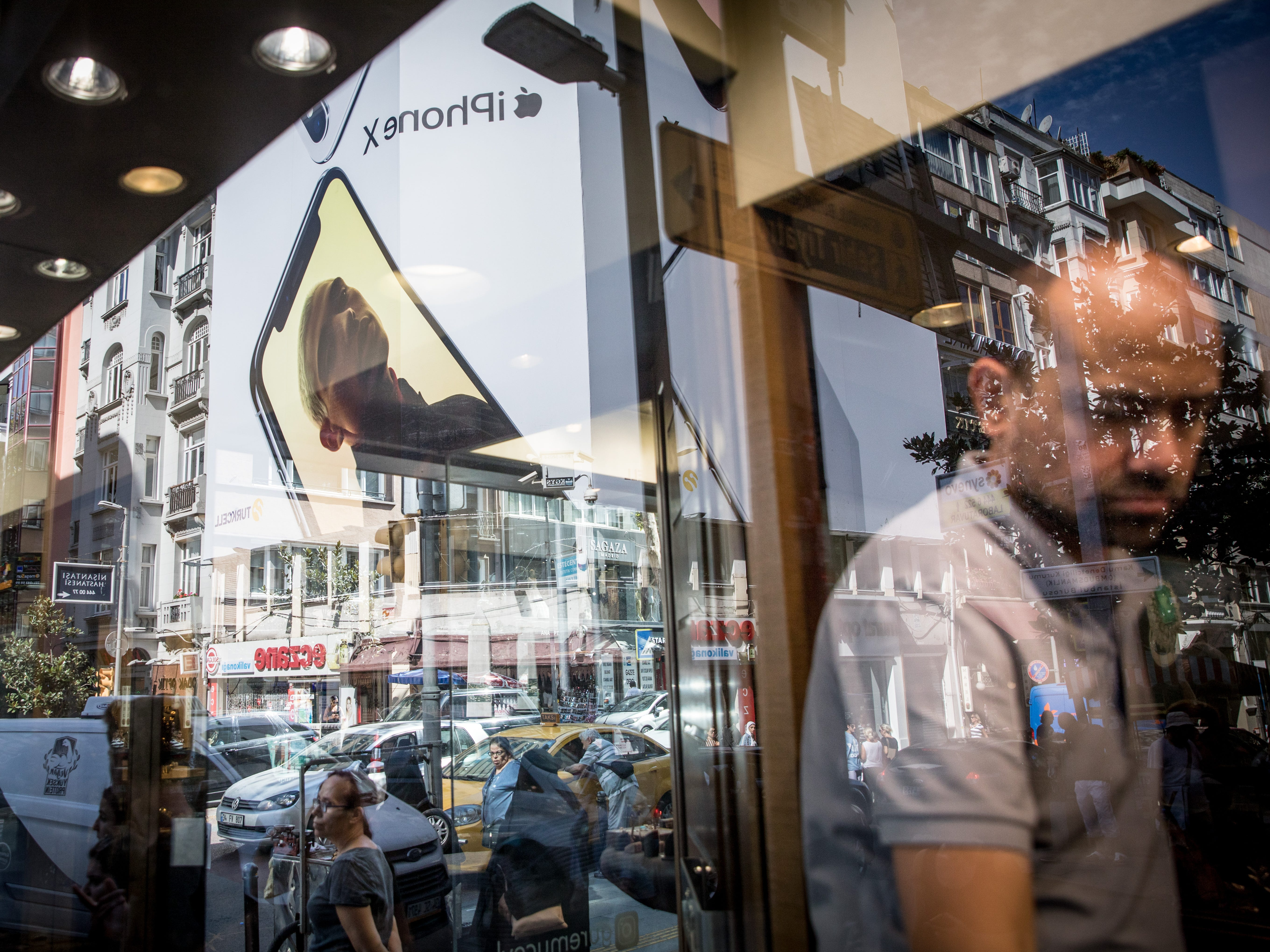 A man works in the window of a jewelery shop as people wait on the street underneath a billboard advertising the Apple iPhone X on Aug. 15, 2018 in Istanbul.