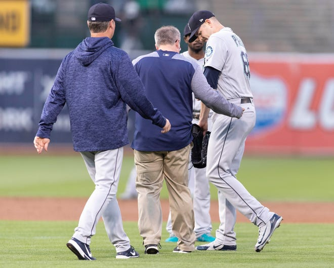 Seattle Mariners starting pitcher James Paxton (65) leaves the field after being hit by a ball during the first inning against the Oakland Athletics at Oakland Coliseum.