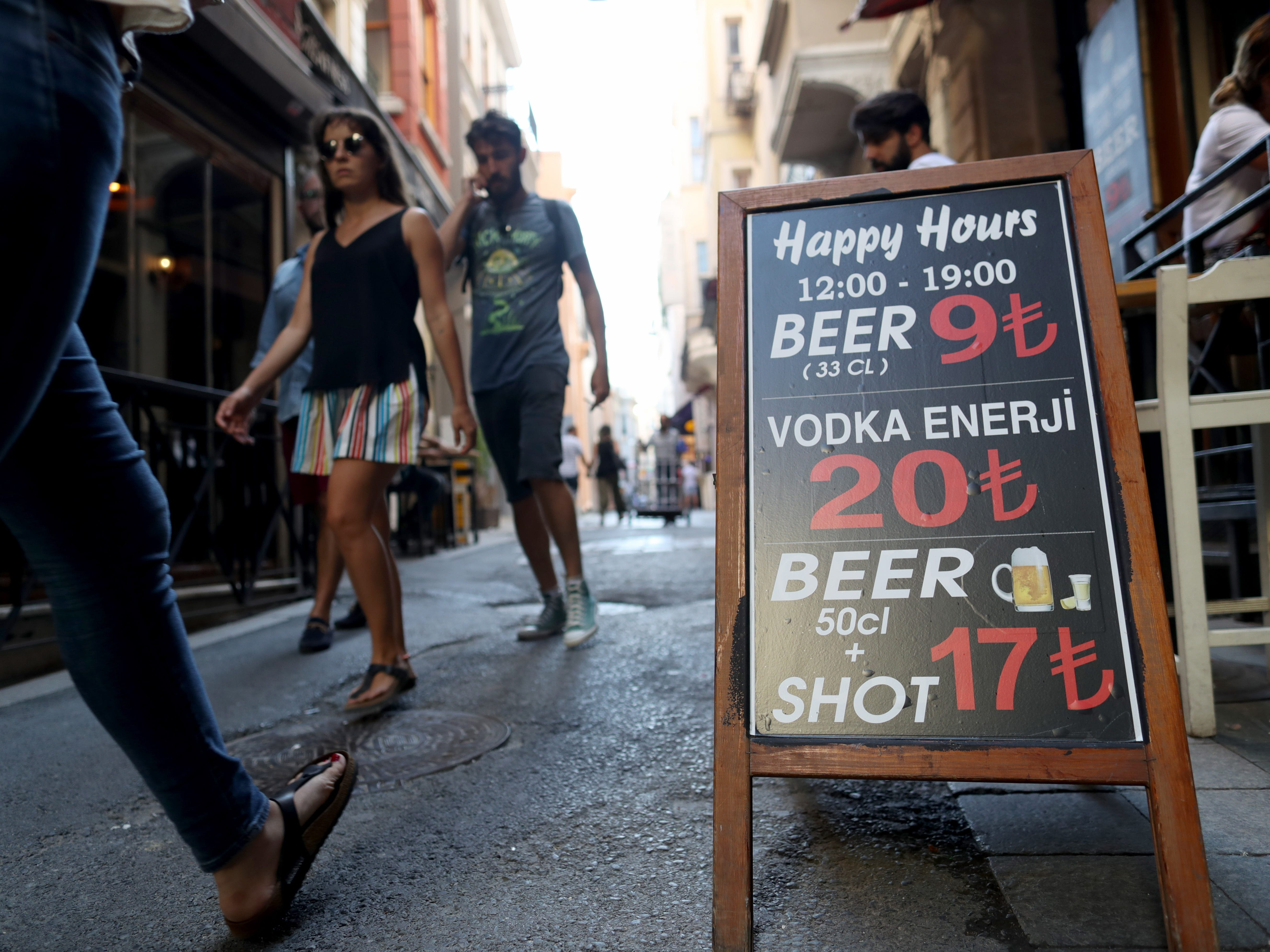 People walk near a pub in Istanbul, Aug. 15, 2018. The Turkish lira has nosedived in value in the past week, but some Turks are reacting with defiance to their plunging currency and an escalating trade and political dispute with the United States.