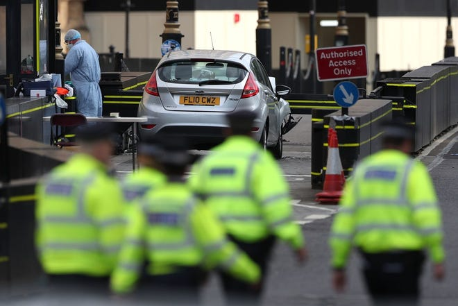 A police forensics officer works around a silver Ford Fiesta car that was driven into a barrier at the Houses of Parliament in central London on August 14, 2018.