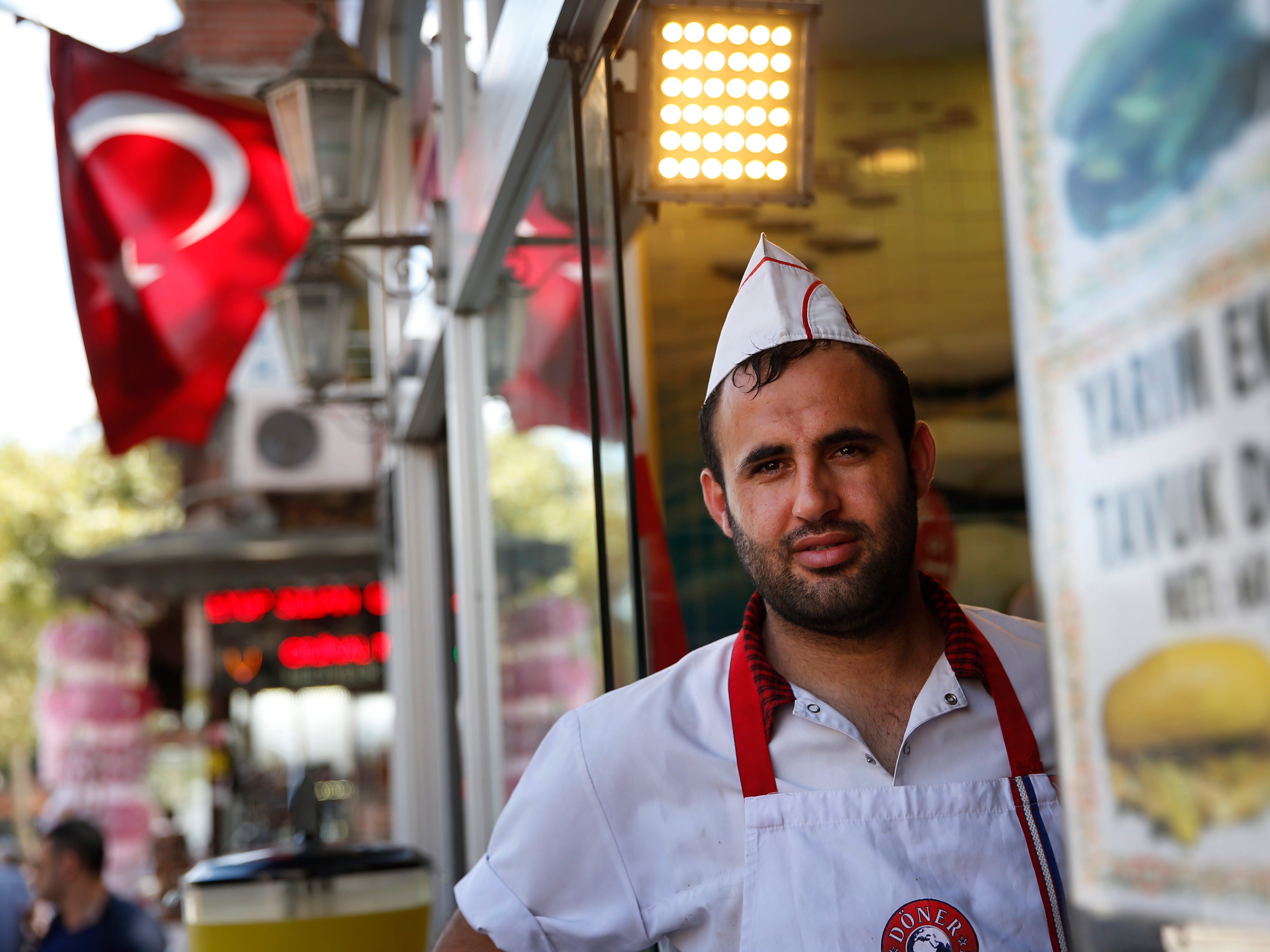 A restaurant worker poses for a photograph in Istanbul, Aug. 15, 2018. Turkish President Erdogan says Turkey will boycott U.S. electronic goods, including Apple's iPhone and slapped an additional tax on imports of American goods from cars to rice to alcohol.
