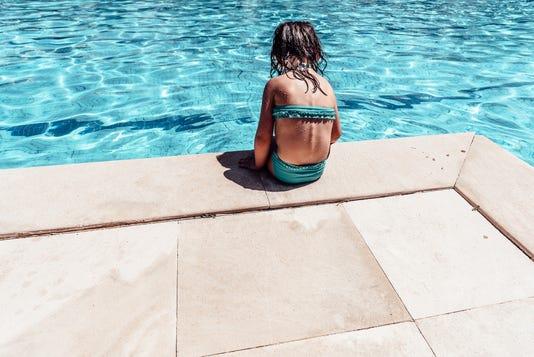 Little Pensive Girl In Bikini Sitting Alone At Swimming Pool