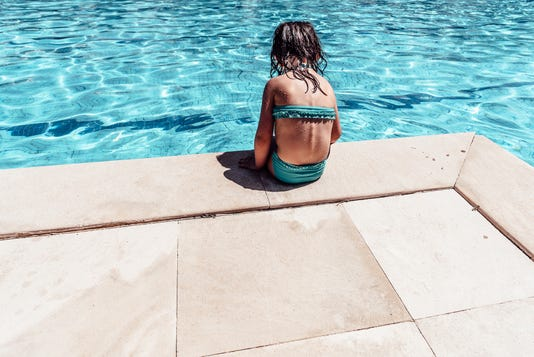 Little Pensive Girl In Bikini Sitting Alone At Swimming Pool