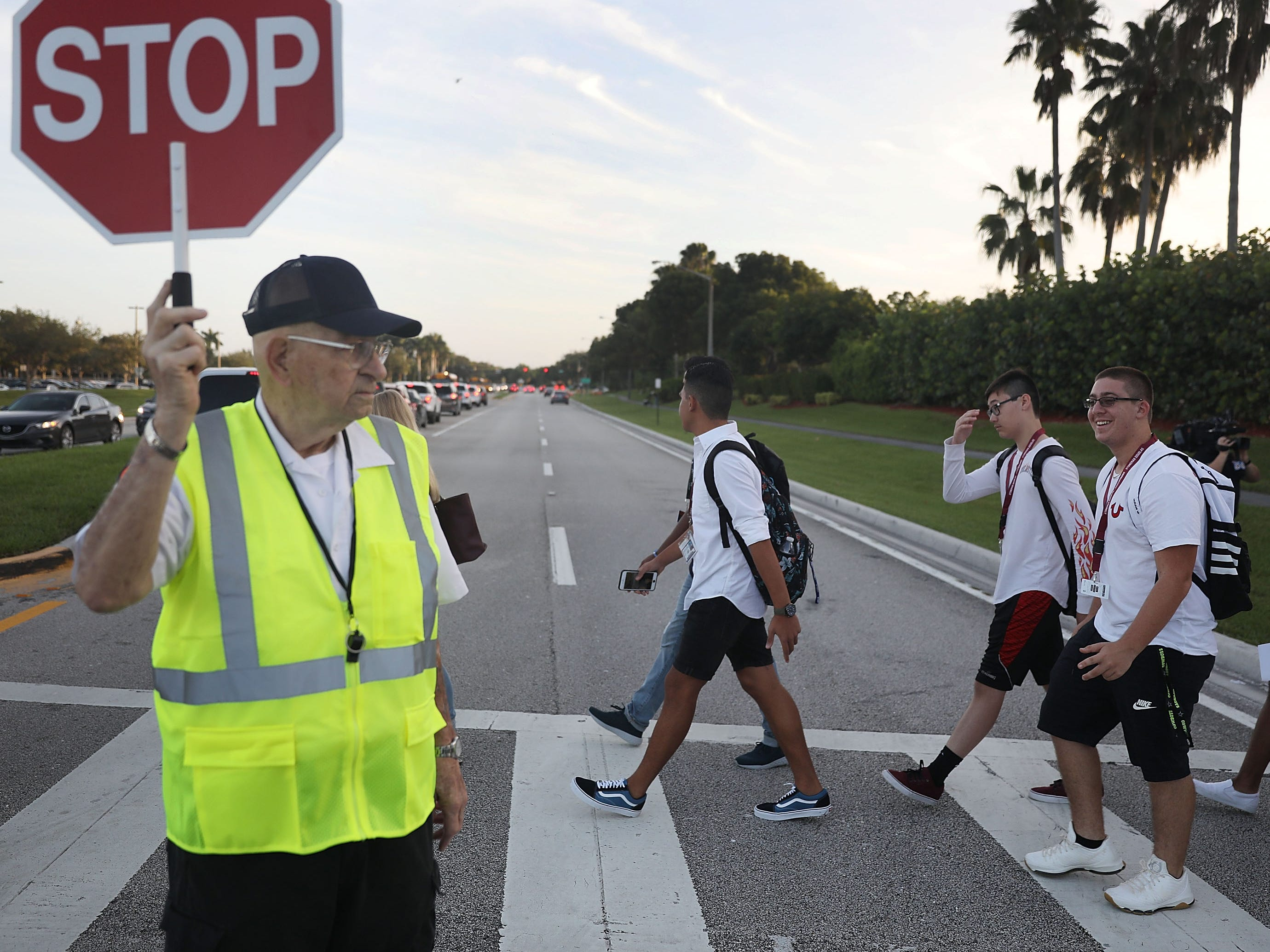 School crossing guard Tony Sorrentino helps students as they walk to Marjory Stoneman Douglas High School on the first day of school on Aug. 15, 2018 in Parkland, Fla.