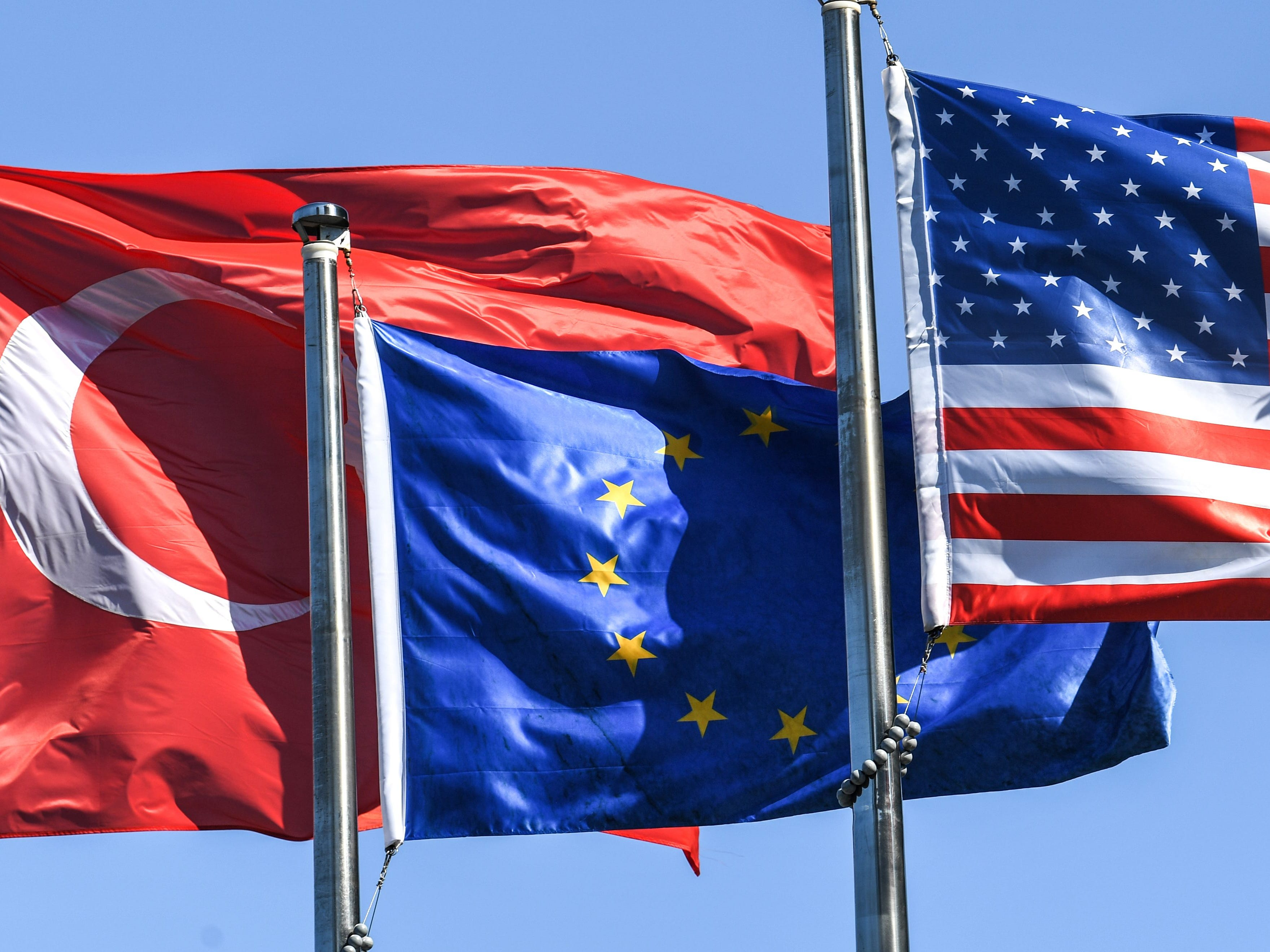 From left, the Turkish flag, European Union's flag and U.S. flag fly in the wind at the financial and business district Maslak on Aug. 15, 2018 in Istanbul.