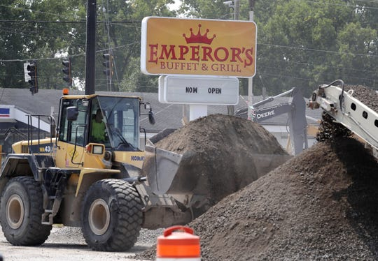 """A sign for Emperor's Buffet & Grill reads """"now open"""" as dirt from construction on Oneida Street is piled nearby."""