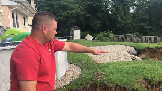 Shawn Dunphy gestures to the landslide that consumed portions of his backyard on Aug. 13.