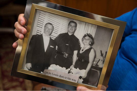 Portella holds a photo picturing him and his parents in 1963, the same year he joined the Newark Police Department.