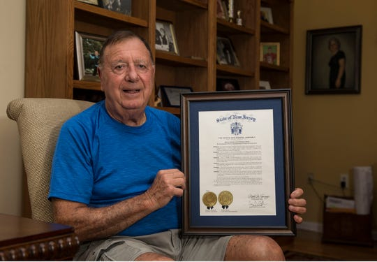 Portella holds a commendation he received from the New Jersey State Legislature.