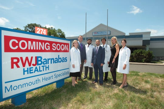 Dr. Isaac Tawfik, (center) chief of cardiology at Monmouth Medical Center stands with the other members of Monmouth Heart Specialists, in front of their new location at 274 Highway 35 in Eatontown.  From left are cardiologists Dr. Lynne Einbinder, Dr. Peter Farrugia, Dr. Haris Usman, Dr. Ajay Shah, and Dr. Julie Master and nurse practitioner Patricia Panfile.