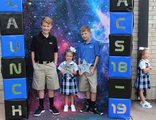 Izzie Baldridge, right, rolls her eyes and wants no part of the family photo before the start of school Thursday at Abilene Christian School. Her twin, Andie, holds her pre-kindergarten star, flanked by seventh-grader Hobs and fifth-grader Penn. Their parents are Stephen and Hollie Baldridge.