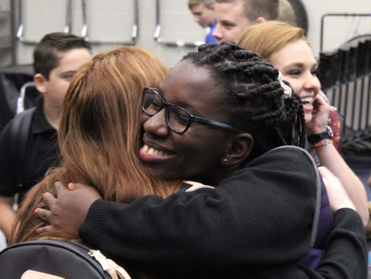 Jochabed Oduro, a junior at Abilene Christian High School from Ghana, hugs a friend as secondary students gather Thursday before the start of the first day of classes.