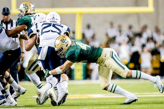 Former Wylie and current Baylor linebacker Clay Johnston tackles West Virginia's Justin Crawford during a 2017 game. Jonhston is a starting linebacker for the Bears in 2018.