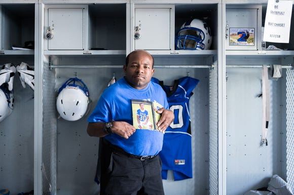 Marshall Lipscomb, the uncle of Markell Lipscomb, stands in front of his locker at Polk County high school holding a photo of him. Markell Lipscomb, a rising senior and a member of the football team, was killed in a car accident in July at the age of 17.