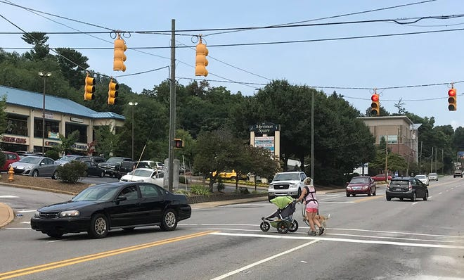 A woman pushes a baby stroller across Merrimon Avenue at the Edgewood Road intersection.
